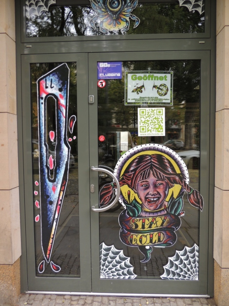 Tattoo studio window with graphic designs.