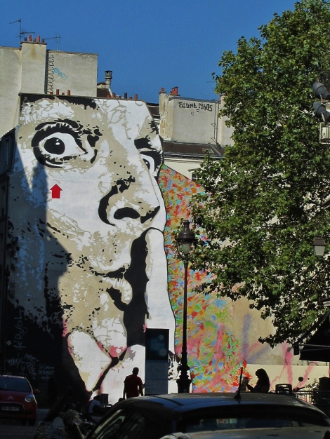 Face mural with rainbow graffiti in Paris
