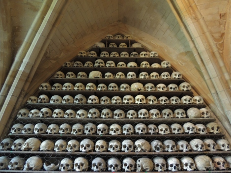 Shelves full of skulls in a stone crypt with vaulted ceilings