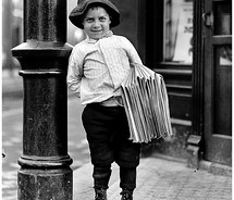 retro newspaper selling boy next to lamppost