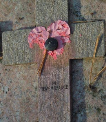 Disintegrating paper poppy on wooden cross