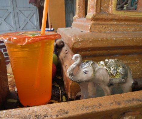 Orange drink in Buddhist offering with elephants