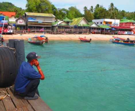 Man waiting on the pier at Koh Tao in front of boats