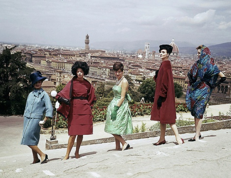 Stylish women posing on the steps against Italian skyline. Retro 1960s