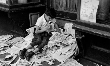 Boy reading pile of newspapers